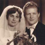 Fotografia przedstawia parę młodą pozującą do zdjęcia - portret. Panna młoda trzyma róże.