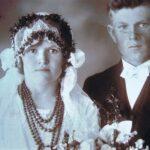 Fotografia przedstawia młodą parę pozującą do zdjęcia. Panna młoda ma na szyi korale.