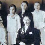 Fotografia przedstawia młodą parę pozującą do zdjęcia wraz z innymi członkami rodziny: trzema kobietami i trzema mężczyznami.