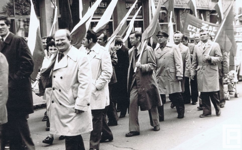 Fotografia przedstawia grupę ludzi z flagami narodowymi, którzy idą w pochodzie. W tle widoczne szyldy sklepowe.
