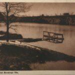 Fotografia przedstawia zbiornik wodny, przy którym zamontowano drewniany pomost. Widoczny rząd kajaków odwróconych dnem do góry.