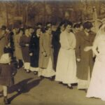 Fotografia przedstawia orszak weselny – na czele para młoda, za nimi parami reszta gości. Z boku idą dwie małe dziewczynki w chustkach na głowie. W tle widoczny mur oraz znak PKS zamocowany na przystanku.