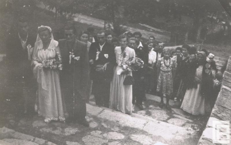 Fotografia przedstawia parę młodą idącą po schodach do kościoła. Z tyłu widoczna liczna grupa gości weselnych.
