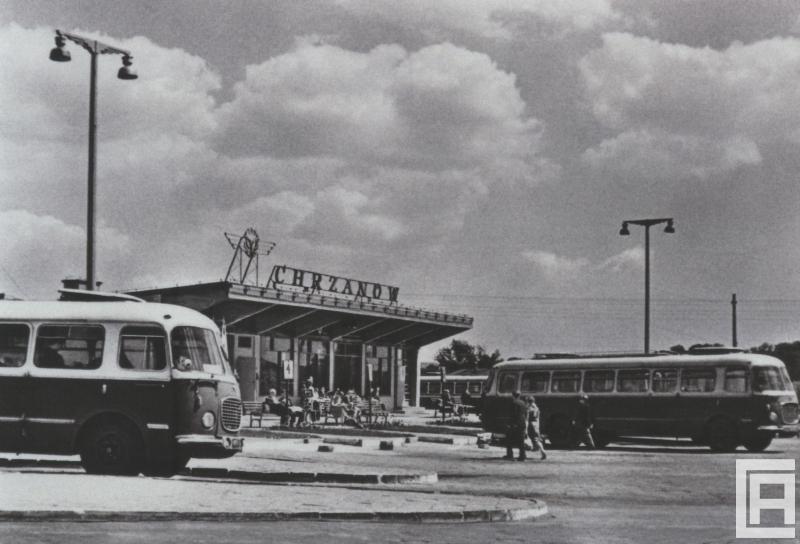 """Fotografia przedstawia zabudowanie dworca z napisem """"Chrzanów"""". Widoczne dwa pojazdy PKS oraz pasażerowie siedzący na ławkach."""
