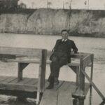 Fotografia przedstawia zbiornik wodny w zalanym kamieniołomie. W tle widoczna przybrzeżna ściana dolomitu. Na pierwszym planie mężczyzna w garniturze pozuje do zdjęcia na ławce na drewnianym pomoście.