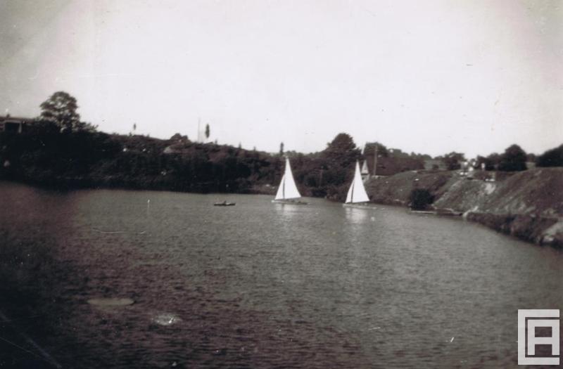 Fotografia przedstawia zbiornik wodny w zalanym kamieniołomie. W centrum zdjęcia zwracają uwagę dwie białe żaglówki.
