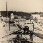 Fotografia przedstawia teren zakładu wydobywczego. W tle komin, linia lasu, kilka budynków. Widoczne tory, wózki z kamieniem. Na pierwszym planie część urządzenia wydobywczego.