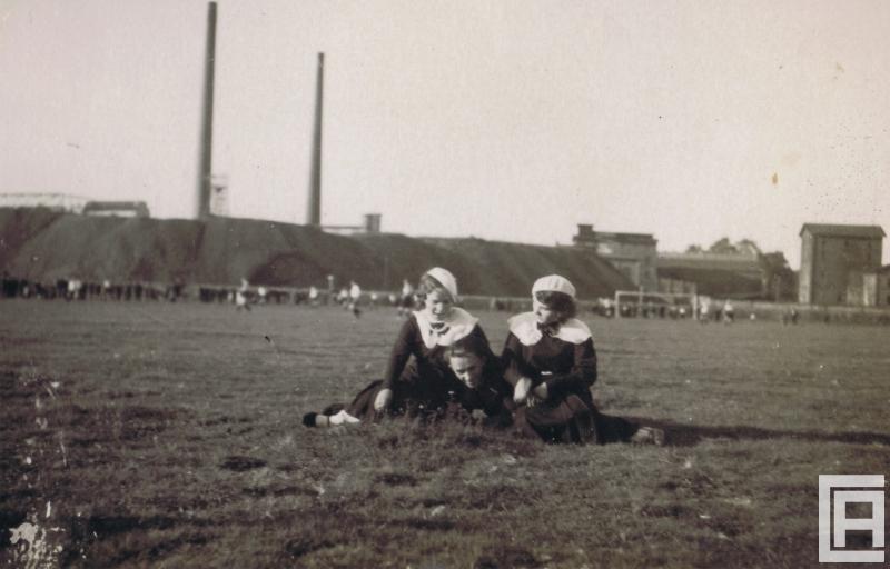 Fotografia przedstawia na pierwszym trzy osoby siedzące na łące. W tle widoczna rozgrywka meczu piłki nożnej oraz zabudowania kopalni.