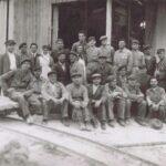 Fotografia przedstawia grupę mężczyzn w ubraniach robotniczych, w środku widoczne dwie kobiety.