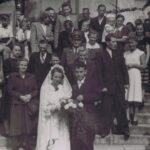 Fotografia przedstawia parę młodą pozującą na schodach kościoła wraz z gośćmi. Z tyłu widoczny mężczyzna w mundurze oraz krzyż przed kościołem.
