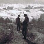 Fotografia przedstawia na pierwszym planie dwóch mężczyzn w mundurach. W tle widoczny teren zakładu wydobywczego.