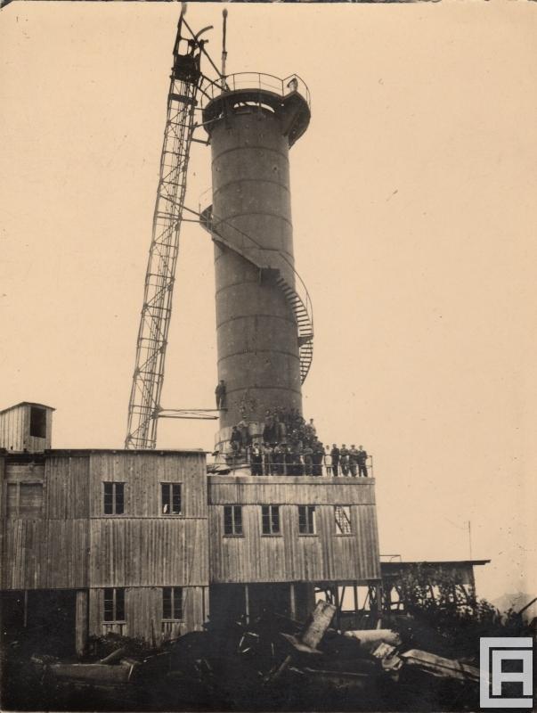 Fotografia przedstawia piec szybowy. U podnóża komina grupa kilkudziesięciu osób.