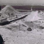 Fotografia przedstawia na pierwszym planie profil kobiety. W tle widoczny teren zakładu wydobywczego.