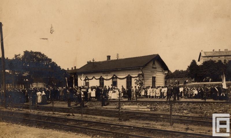 Fotografia przedstawia biały budynek stacji lokalnej z napisem Chrzanów. Z tyłu, wzdłuż peronu i na torach tłum ludzi. Widoczne dekoracje.