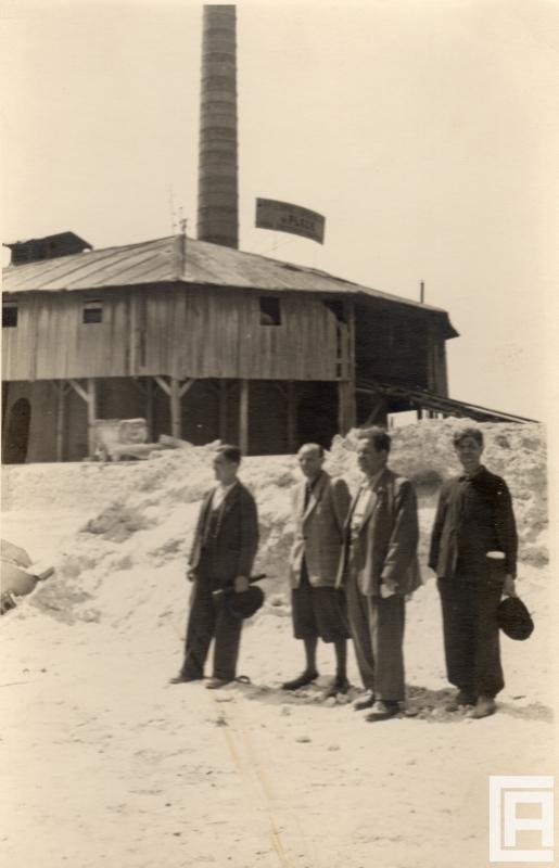 Fotografia przedstawia w tle budynek pieca kręgowego. Na pierwszym planie czterech mężczyzn w garniturach.