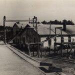 Fotografia przedstawia teren zakładu wydobywczego: zabudowania, rusztowania, rury.