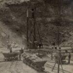 Fotografia przedstawia teren zakładu wydobywczego, widoczne są tory, wagoniki zapełnione kamieniem, pracownicy obsługujący wydobycie, wieża z kołowrotem.