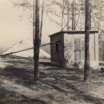 Fotografia przedstawia murowany budynek z rurami w otoczeniu drzew.