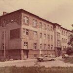 Fotografia przedstawia budynek szpitala. Przed nim dwa samochody i sanitarka.