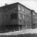 Fotografia przedstawia budynek szpitala. Przed nim przechodzą dwie pielęgniarki.