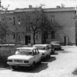 Fotografia przedstawia budynek. Przed nim widoczne cztery samochody osobowe.