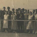 Fotografia przedstawia grupę czternastu osób stojących na korcie, zaraz za siatką do gry w tenisa. Przynajmniej cztery z nich trzymają rakiety. Mężczyzna na środku ma w rękach puchar.