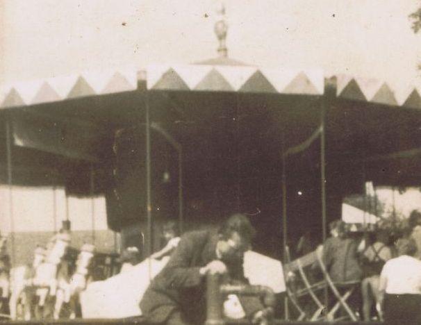 Fotografia przedstawia mężczyznę korzystającego z pompy. W tle widoczna karuzela z konikami.
