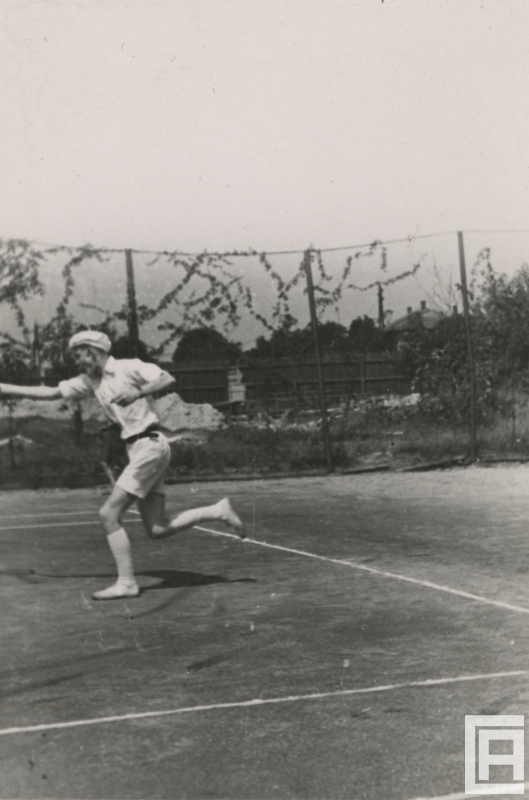 Fotografia przedstawia mężczyznę grającego w tenisa. Rakieta poza kadrem.