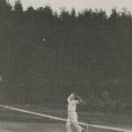 Fotografia przedstawia mężczyznę grającego w tenisa. Właśnie szykuje się do odbicia lecącej z góry piłki.