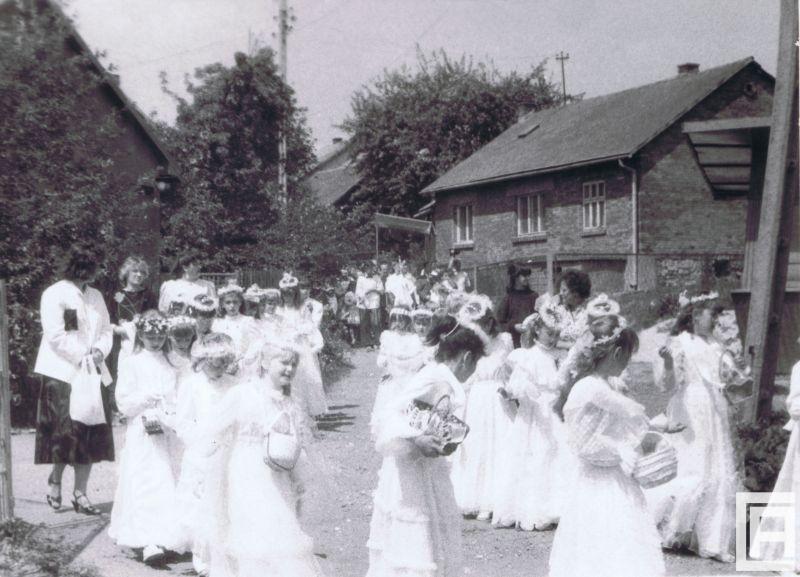 Fotografia przedstawia kilkadziesiąt dziewczynek w strojach z pierwszej komunii świętej, które z koszyczkami ustawiają się w rzędzie. Z boku doglądają ich rodzice. W tle drzewa i murowany budynek.