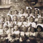 Fotografia przedstawia grupę dziewczynek w odświętnych ubraniach ze złożonymi do modlitwy rękami i koszyczkami.