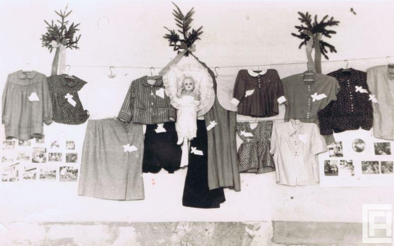 Fotografia przedstawia kolekcję ubrań dziecięcych zawieszonych na wieszakach na lince na ścianie. Widoczne także ilustracje, lalka, gałązki z drzew iglastych.