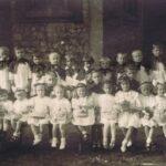 Fotografia przedstawia grupę odświętnie ubranych dziewczynek i chłopców - trzymają odpowiednio koszyczki z kwiatami oraz dzwonki. Z lewej stoi siostra zakonna, z prawej - ksiądz.