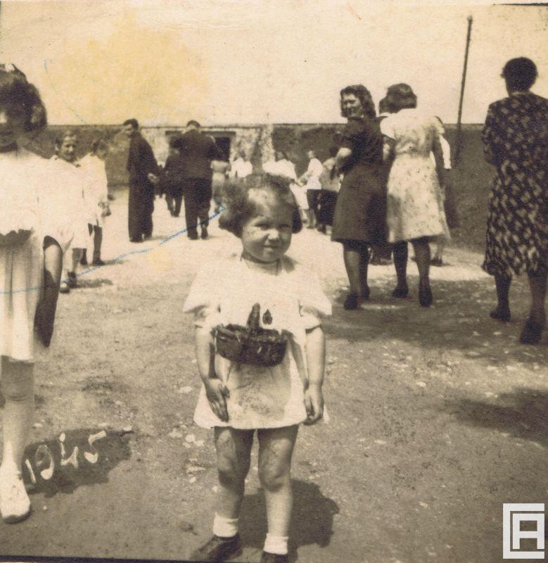 Fotografia przedstawia grupę ludzi idących w kierunku wiaduktu kolejowego. Na pierwszym planie dziewczynka w białej sukience z koszyczkiem.