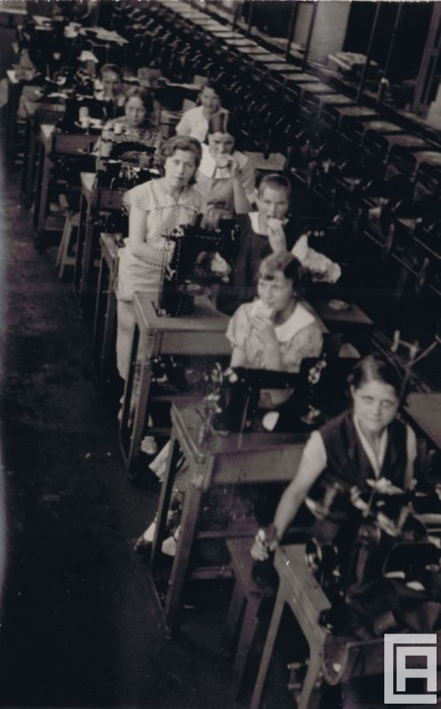 Fotografia przedstawia rząd stanowisk z maszynami do szycia, przy których siedzą kobiety - na hali przemysłowej.