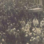 Fotografia przedstawia tłum ludzi idących w procesji za monstrancją widoczną po prawej stronie, pod baldachimem.