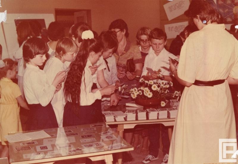 Fotografia przedstawia grupę osób zebranych na wystawie. Na pierwszym planie oszklony stół z wystawą grafik, w głębi stoisko z ekslibrisami i zakładkami bibliotecznymi, które zabierają odwiedzający.
