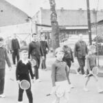 Fotografia przedstawia grupę idących osób: dorosłych w strojach sportowych oraz młodzież trzymającą rakiety tenisowe.