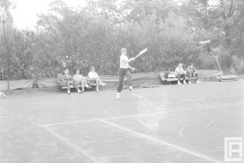Fotografia przedstawia osobę zamachującą się rakietą tenisową podczas gry. Z tyłu na dwóch ławkach siedzi pięć osób.