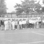 """Fotografia przedstawia grupę osób pozującą do zdjęcia na korcie tenisowym. Na płocie napis """"Witamy uczestników Spartakiady""""."""