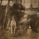 Fotografia przedstawia trzech mężczyzn na sianie popijających piwo ze szklanek. Obok siedzi pies.