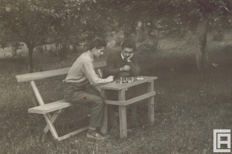 Fotografia przedstawia dwóch mężczyzn w sadzie siedzących na ławce. Pochylają się nad szachownicą postawioną na drewnianym stole.