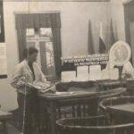 Fotografia przedstawia świetlicę Zakładowego Domu Kultury: kobieta zbiera gazety ze stolików. Na stolikach wmontowana szachownica. W tle widoczny napis: Razem młodzi przyjaciele - w szczęściu wszystkiego są wszystkich cele.