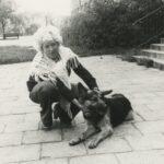 Fotografia przedstawia kucającą kobietę, która głaszcze leżącego psa.