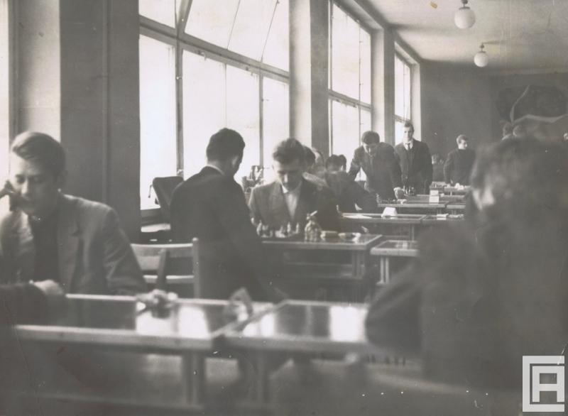Fotografia przedstawia graczy przy szachownicach rozmieszczonych na podwójnie zestawionych stolikach wzdłuż okien.
