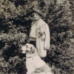 Fotografia przedstawia mężczyznę w stroju góralskim w towarzystwie psa.