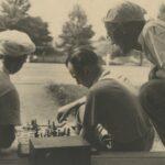 Fotografia przedstawia dwóch mężczyzn obróconych plecami do aparatu, którzy grają w szachy - prawdopodobnie na schodkach na wolnym powietrzu. Trzeci mężczyzna nachyla się z prawej i przygląda grze.