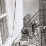 Fotografia przedstawia chłopca siedzącego w rogu balkonu, obok siedzi mały pies.