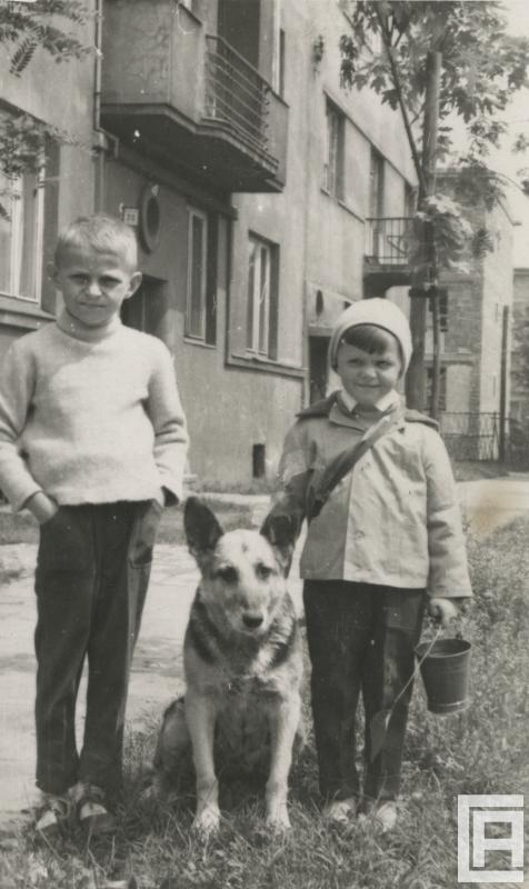 Fotografia przedstawia dwóch chłopców. Między nimi siedzi pies. W tle widoczny budynek.