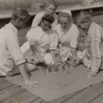 Fotografia przedstawia grupę pięciu osób siedzących przy szachownicy na kocu, na drewnianej podłodze. Jedna z kobiet ma na głowie czepek pielęgniarski.